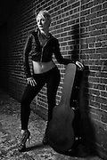 Beautiful, sexy woman in black leather and pants with guitar case in an alley