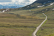 View of the Park Road and Denali Mountain as it crosses the tundra at Stony Hill Overlook in Denali National Park Alaska. Denali National Park and Preserve encompasses 6 million acres of Alaska's interior wilderness.