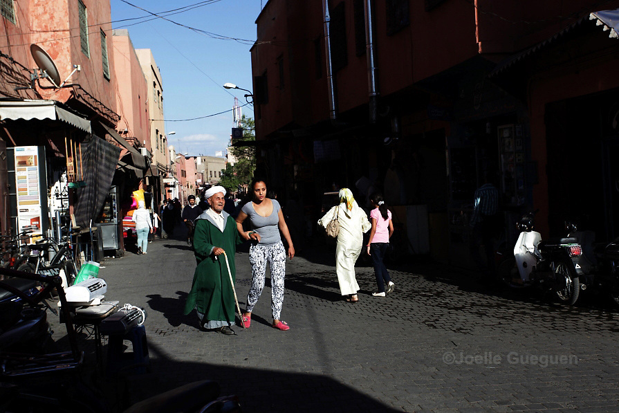 Rachida single mother, 32 years old helps an old blind man to ease his way towards Bab Doukala- Marrakech May 2013