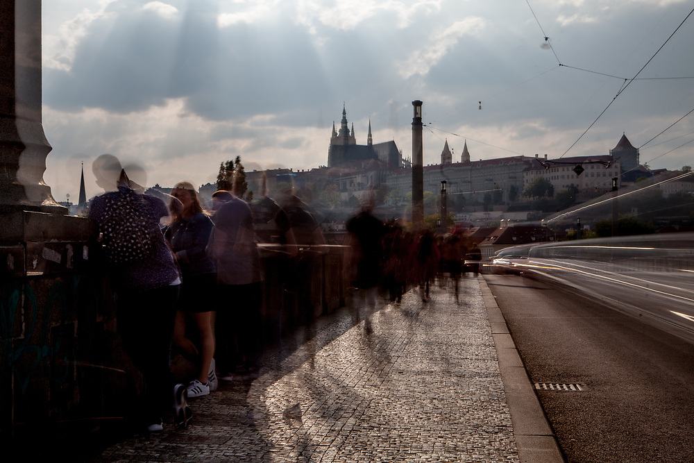 "Crowds passing ""Manesuv Most"" with Prague Castle in the back."