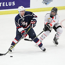 COBOURG, - Dec 16, 2015 -  Game #7 - United States vs Switzerland at the 2015 World Junior A Challenge at the Cobourg Community Centre, ON. Callahan Burke #11 of Team United States keeps the puck from Dominik Volejnicek #11 of Team Switzerland during the first period.(Photo: Tim Bates / OJHL Images)