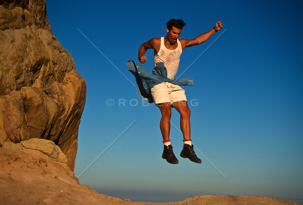 Man jumping from a rock formation in a celebratory gesture