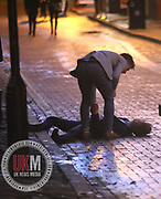 Manchester UK  24.12.2016: Images from Manchesters Gay Village during the Mad Friday celebrations this on the 23 and 24th of December,<br /> <br /> A man layed out on the street as a  friend looks on