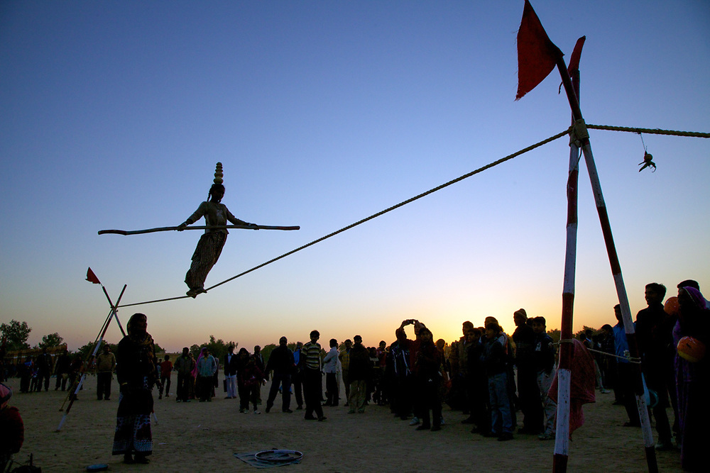 Rajasthan, India. A 12 years old indian girl is performing tightrope walking in front spectators at the Desert Festival in Jaisalmer.<br />