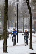Twee jongens rijden op de Zijpendaalseweg in Arnhem door de sneeuw.<br /> <br /> Two boys are cycling at the Zijpendaalseweg in Arnhem in the snow.