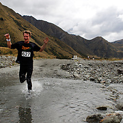 Runner Tom Rhodes crosses Moke Creek on the Ben Lomond High Country Station during the Pure South Shotover Moonlight Mountain Marathon and trail runs. Moke Lake, Queenstown, New Zealand. 4th February 2012. Photo Tim Clayton