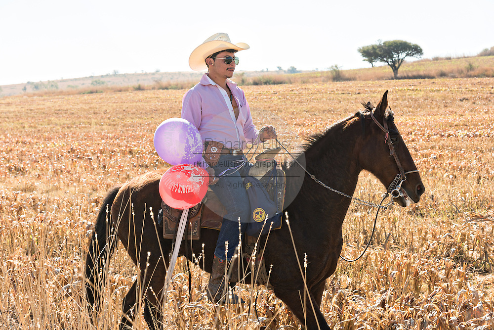 A Mexican cowboy holds balloons given him by villagers as hundreds of horsemen ride during the annual Cabalgata de Cristo Rey pilgrimage January 5, 2017 in La Trinidad, Guanajuato, Mexico. Thousands of Mexican cowboys and horse take part in the three-day ride to the mountaintop shrine of Cristo Rey stopping along the way at shrines and churches.