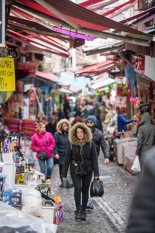 Awnings provide coverages to shoppers walking along narrow stone street lined with shops selling various goods, Istanbul, Turkey