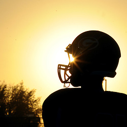 A Glendora player is silhouetted prior to a prep football game against Los Altos at Citrus College in Glendora, Calif., Friday, Sept. 18, 2015.