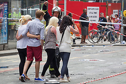 © Licensed to London News Pictures . FILE PICTURE DATED 15/07/2013 . Oldham Street , Manchester , UK . Stephen Hunt's family arrive at the scene . Son Sam (maroon shorts , 15), daughter Charlotte (black and white sleeveless top, black pants, 18), sister Sarah (cream sleeveless top, blue jeans, dark hair, sunglasses) and ex-wife Zoe (white top, black pants, sunglasses) . The scene on Oldham Street following a fire at Paul 's Hair World on 13th July which claimed the life of fireman Stephen Hunt . Photo credit : Joel Goodman/LNP