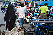 09 JULY 2013 - PATTANI, PATTANI, THAILAND: A Muslim woman walks down the street in the market in Pattani.  Pattani, along with Narathiwat and Yala, are the only three Muslim majority provinces in Thailand.     PHOTO BY JACK KURTZ