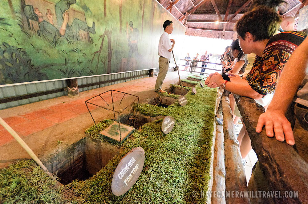 A tour guide explains a range of different booby traps used as anti-personnel defenses in the area during the war. The Cu Chi tunnels, northwest of Ho Chi Minh City, were part of a much larger underground tunnel network used by the Viet Cong in the Vietnam War. Part of the original tunnel system has been preserved as a tourist attraction where visitors can go down into the narrow tunnels and see exhibits on the defense precautions and daily life of the Vietnamese who lived and fought there.