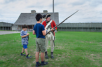Reenactment soldier demonstration musket to two young boys. Colonial Michilimackinac, Mackinaw City Michigan.