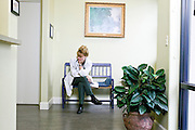 Female doctor in white lab coat sitting with legs crossed resting her head on her hand in the lobby of a medical office, Tucson, Arizona...Media Usage:.Subject photograph(s) are copyrighted Edward McCain. All rights are reserved except those specifically granted by McCain Photography in writing...McCain Photography.211 S 4th Avenue.Tucson, AZ 85701-2103.(520) 623-1998.mobile: (520) 990-0999.fax: (520) 623-1190.http://www.mccainphoto.com.edward@mccainphoto.com
