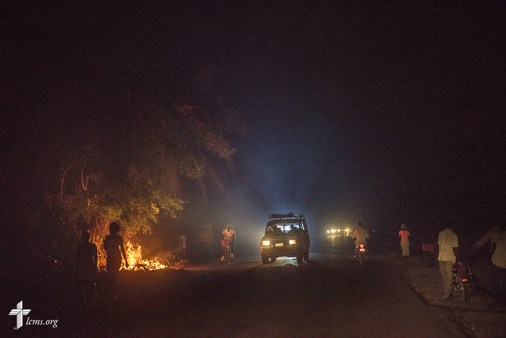 A light truck navigates a street at night shrouded in thick smoke from debris fires on Tuesday, Oct. 11, 2016, in Les Cayes, Haiti. LCMS Communications/Erik M. Lunsford