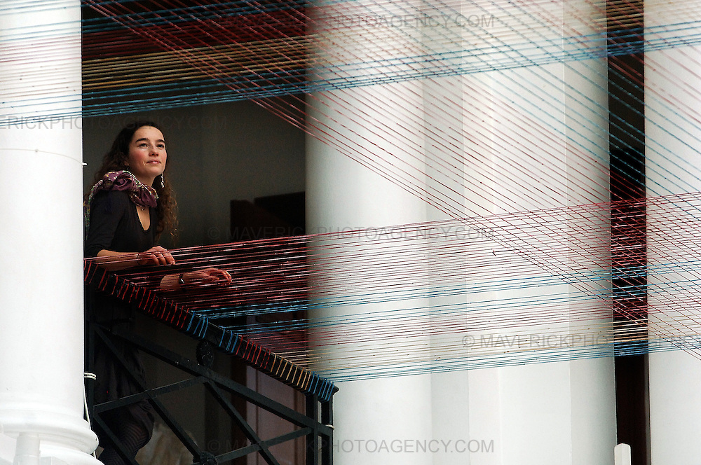Edinburgh College of Art Master of Fine Art student Daniela Justiniano has created the latest in a series of rubber bands installations, a vast elastic tartan, in the College Sculpture Court. The work has been made with 25,350 colored elastic bands. The 27 year old artist from Santiago, Chile, spent three weeks assembling the work and installing the elastic chains across the balcony of the Sculpture Court.