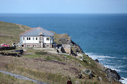 Newquay, Cornwall, England, UK, Wednesday 25th March 2015.  Lewinnick Lodge undergoes some chimney rennovation as it perches next to the cliff in Pentire on the East Headland on Newquay Bay.