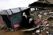 Palestinian women  Saba Siam helps her family member from the Siam family in makeshift shelter she built across from  the rubble by their home in the Abd Rabo neighborhood of Gaza where most of the neighborhood was completely destroyed by the Israeli army during the Israeli invasion into the Gaza Strip last winter .(Photo by Heidi Levine/Sipa Press).