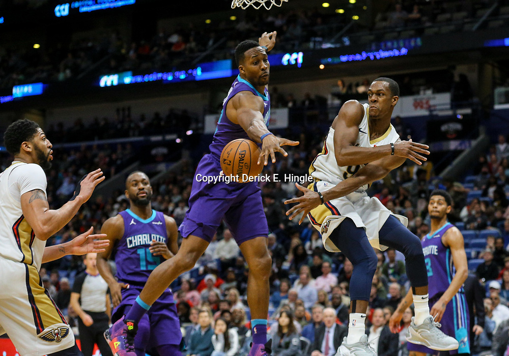 Mar 13, 2018; New Orleans, LA, USA; New Orleans Pelicans guard Rajon Rondo (9) passes for an assist to forward Anthony Davis (left) as Charlotte Hornets center Dwight Howard (12) defends during the fourth quarter of a game at the Smoothie King Center. The Pelicans defeated the Hornets 119-115.  Mandatory Credit: Derick E. Hingle-USA TODAY Sports