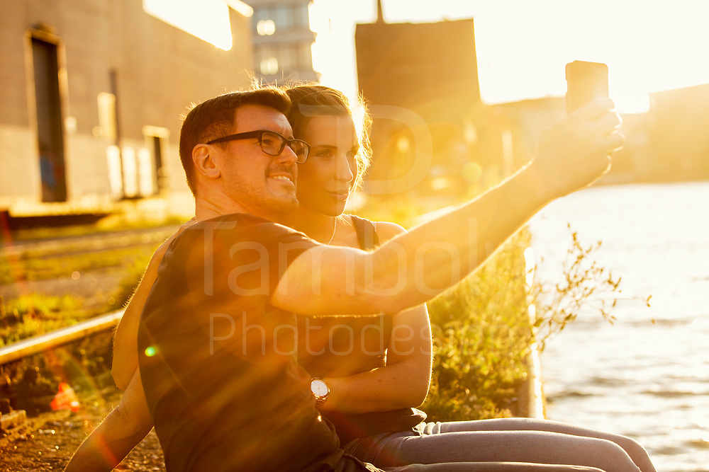 couple on the harbor of münster taking a selfie with a smartphone.