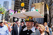 New York, NY - April 16, 2017. A man wears a bowler topped with a platform with dolls and toys at New York's annual Easter Bonnet Parade and Festival on Fifth Avenue.