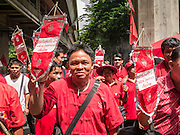 19 MAY 2013 - BANGKOK, THAILAND: Thai Red Shirts march down Rama I Road in Bangkok during a Red Shirt rally honoring Red Shirts killed by the Thai army in 2010. More than 85 people, most of them civilians, were killed during the Thai army crackdown against the Red Shirt protesters in April and May 2010. The Red Shirts were protesting against the government of Abhisit Vejjajiva, a member of the opposition who became Prime Minister after Thai courts ruled the Red Shirt supported government was unconstitutional. The protests rocked Bangkok from March 2010 until May 19, 2010 when Thai troops swept through the protest areas arresting hundreds.    PHOTO BY JACK KURTZ