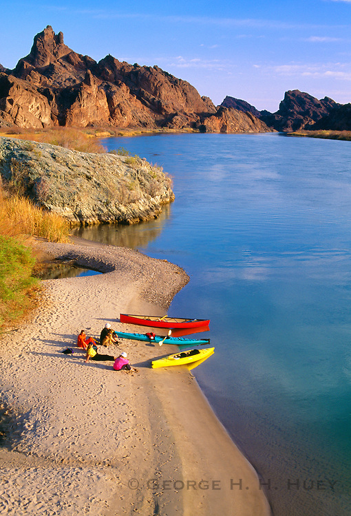 350166-1014 ~ Copyright: George H. H. Huey ~ Canoes and kayak in Topock Gorge, Colorado River with visitors on beach. Needles Wilderness in background. Havasu National Wildlife Refuge, Arizona.