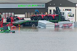© Licensed to London News Pictures. 16/02/2020.  Builth Wells, Powys, Wales, UK. Quad bike are rescued at Smithfield tractors. The river Wye bursts it's banks at Builth Wells in Powys, Wales, UK. after heavy rainfall yesterday and last night, causing the A483 road to be closed and traffic diverted. The river level broke the all-time high (5.05 m) at 08.30hrs  this morning at Builth Wells. According to Natural Resources Wales the highest recorded level at Builth Wells was 4.95m on 28/10/98 at 2:45 am (GMT) Photo credit: Graham M. Lawrence/LNP