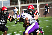 Colton Feller '14, right, wraps up a Knox College rusher during last Saturday's 43-35 victory at Rosenbloom Field.