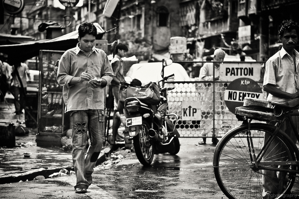 A young man walks down a crowded Kolkata (Calcutta) street. Converted to black and white using Silver Efex Pro.