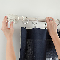 How to hang curtains: inserting curtain rod into bracket and attaching finial