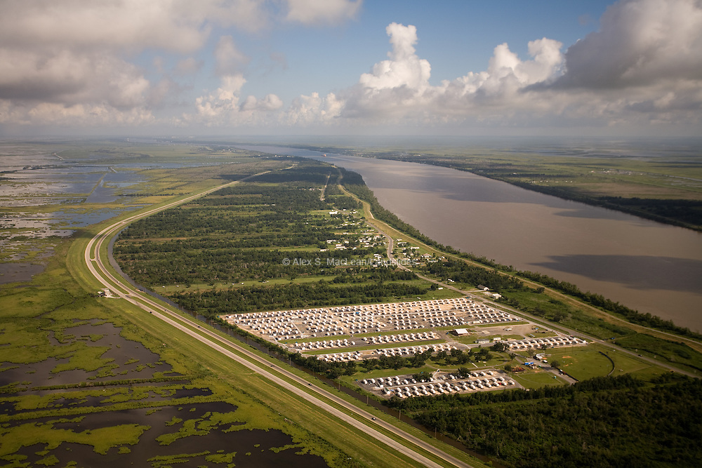 The Mississippi River is the largest inland shipping waterway in the United States.  Rows of Federal Emergency Management Agency (FEMA) trailers form a small community on a natural embankment of the Mississippi River.  Situated between two levies, the FEMA trailers continue to provide shelter for survivors nearly two years after Hurricane Katrina.