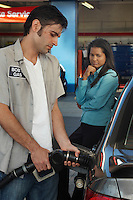 Woman watching gas station attendant pumping gas