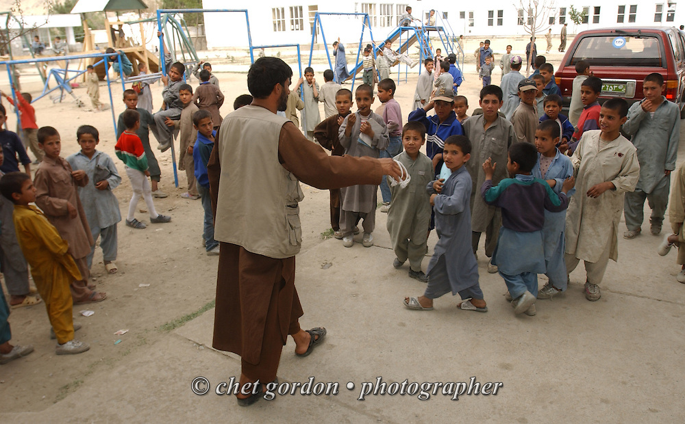 "A counselor scatters Afghan orphan boys outside the Alowdin Orphanage for boys and girls on Saturday, May 25, 2002. A humanitarian mission organized by The Geshundheit Instititute, founded by Dr. Hunter ""Patch"" Adams, Lufthansa Cargo, and DHL Worldwide Express collaborated to ship medicines, food and orthopedic supplies to the Indira Ghandi Children's Hospital, clinics and orphanages in Kabul. The German NGO (Non Governmental Organization) Hammer Forum supervised the distribution of the donated supplies from various non-profit organizations in the U.S. and The Netherlands."