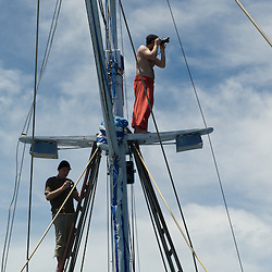 Photographers on the mast construction of a sailing boat.