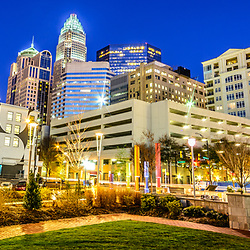 Charlotte North Carolina skyline at night panorama photo with Romare Bearden Park and downtown Charlotte buildings against a blue sky. Panorama photo ratio is 1:3. Charlotte, NC is a major city in North Carolina in the Eastern United States of America.