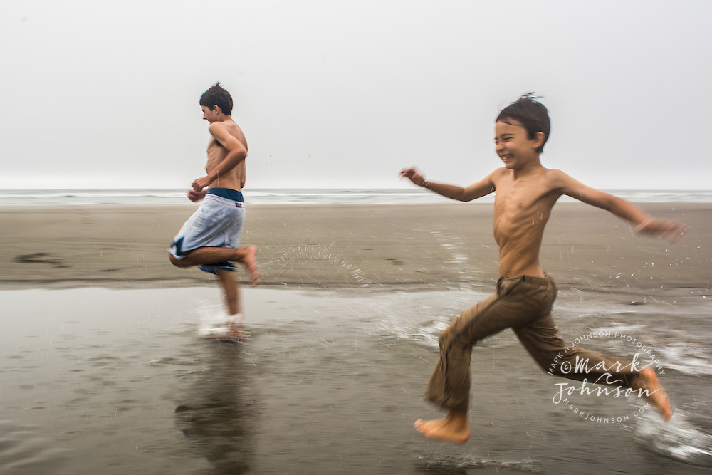2 boys running through water at the beach, Oregon, USA