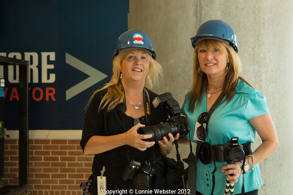 Valerie Lovelace and Sherry Baer City of Charlottes photographers with DNCC hardhats at the behind the scenes media walkthrough of the Time Warner Cable Arena in Charlotte NC. 2012-08-22