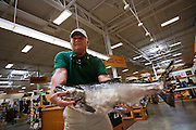 Dan Rife pulls his prize 22 pound Chinook salmon out of the cooler to place it into the storage freezer at Wholesale Sports in Coeur d'Alene on Thursday. Rife caught the fish on the South end of Lake Coeur d'Alene during The Big One Chinook Derby early in the morning.