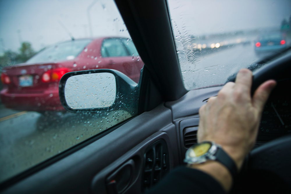 A first person point of view of driving on a freeway in the rain.