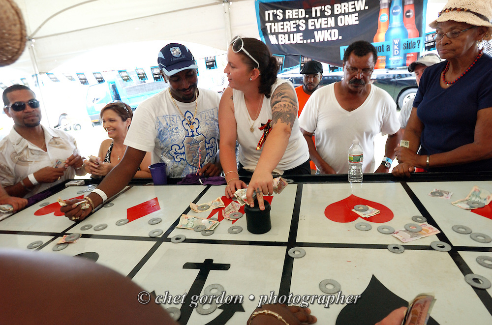 Bermudians play the casino game Crown and Anchor during the first day of Cup Match at the St. George's Cricket Club in St. George's, Bermuda on Thursday, July 28, 2011. The 109th. Annual Cup Match takes place during the two day public holidays of Emancipation Day and Somers Day in Bermuda. Cup Match is the only time when gambling is legal on the island.