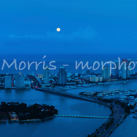 Moonrise over Miami Beach at twilight showing government cut, Port of Miami, south beach and Fisher Island.  This version is watermarked, contact us to license and clean.