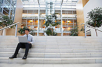 Businessman using laptop on steps outside office