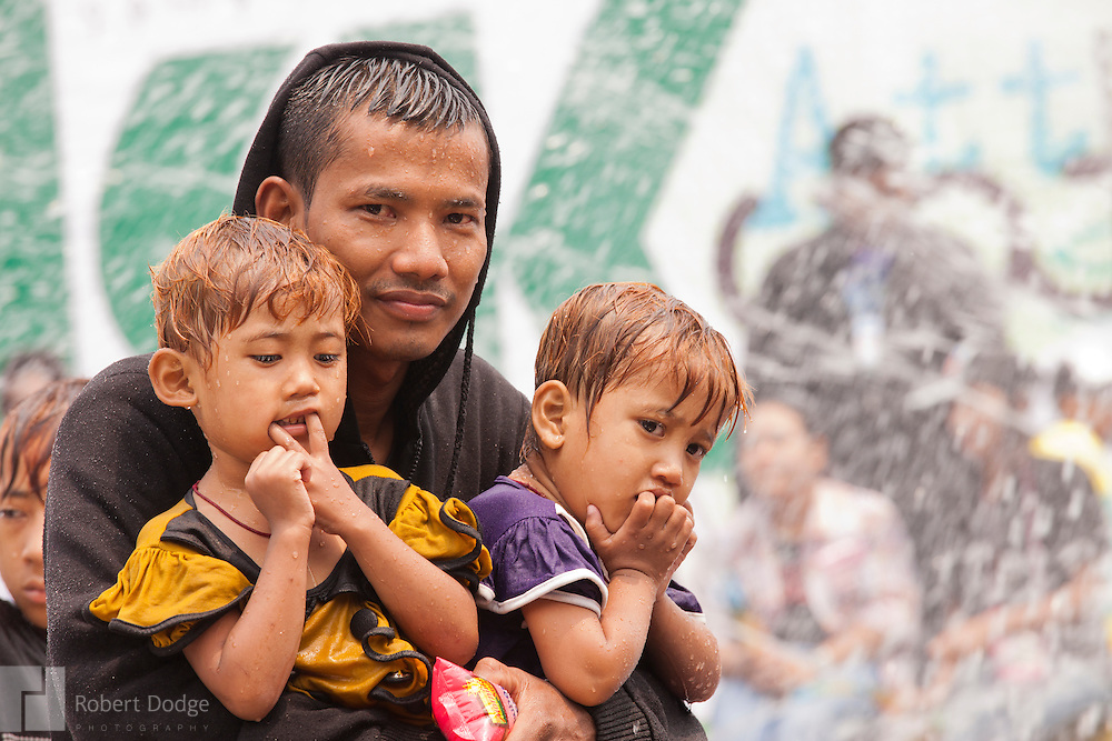 Mandalay, Myanmar- April 14, 2013: A young father holds onto his children during Myanmar's Thingyan Water Festival. Thingyan is held in April, one of the hottest months of the year in Myanmar. The water festival marks the country's New Year celebration and the festival includes lots of drinking, singing, dancing and theater. Wherever you are you are likely to get doused with water as the Burmese see this as a cleansing of the previous year's sins and bad luck and a blessing for good luck and prosperity in the year ahead. In the major cities of Mandalay and Yangon, large platforms are erected along major roadways and are equipped with high powered water hoses. The platforms, sponsored by large corporate donors, also have dance stages and play the latest pop and hip hop music. Thousands of residents pour into the streets by foot, motorbike and flatbed truck to get hosed under the platforms while they drink and dance. Many of the young celebrants wear their best clubbing clothes. And many of the party goers are men, having left their wives and girlfriends at home.