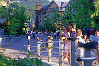 Taylor, 5, plays with the bronze art on the Whistler Village bridge while her dad looks on. Whistler Village summer.