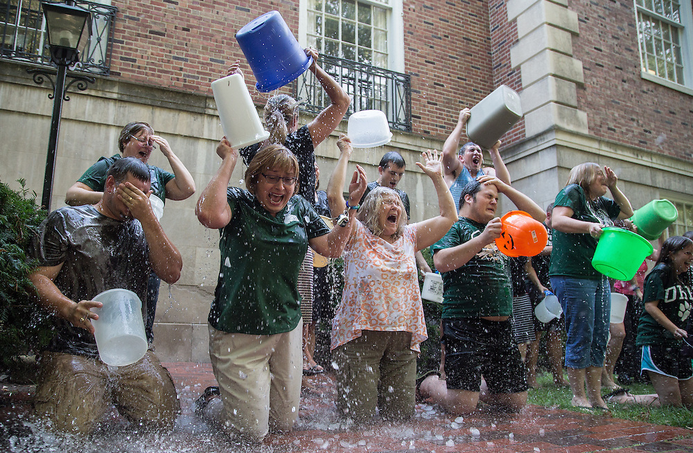 "Employees of the Financial Aid Department react as they pour buckets of ice water over their heads to participate in the ""Ice Bucket Challenge"" in honor of Vicky Boyles, a coworker who was forced to leave her work as the Assistant Director of Financial Aid at the end of last March due to her battle against PMA. The group gathered behind Chubb Hall on College Green on Wednesday, August 27, 2014. Photo by Katelyn Vancouver"