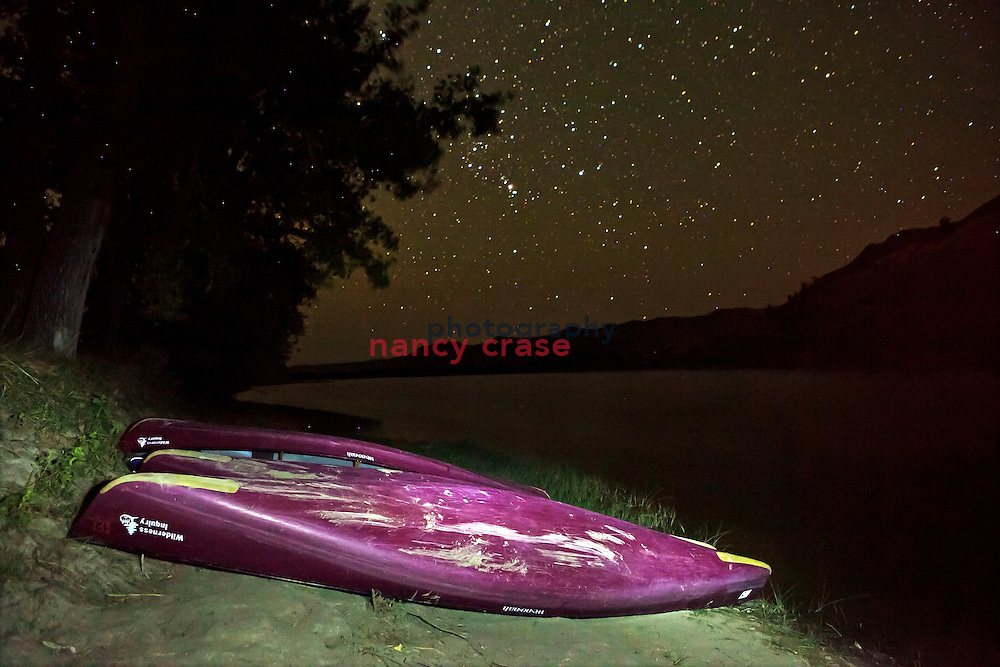 Eleven participants and two guides from Wilderness inquiry canoed the Upper Missouri River Breaks National Monument from Coal Banks to Judith Landing, Montana, from September 4 to 9, 2011.  A few of the canoes rest on the river bank while stars fill the Montana sky.