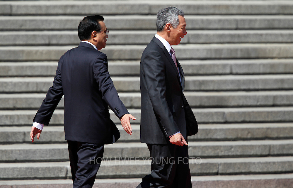 epa03837688 Singapore's Prime Minister Lee Hsien Loong (L) walks with Chinese Premier Li Keqiang during a welcome ceremony at the Great Hall of the People in Beijing, China, 26 August 2013. Lee is on a seven-day visit to China where he will also visit China's Xinjiang Uygur Autonomous Region and Liaoning Province.  EPA/HOW HWEE YOUNG