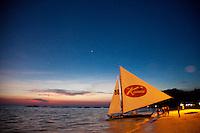 Sailboat sitting on white sand beach boracay at night.