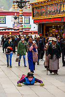 A Tibetan woman prostrates herself, as other pilgrims circumambulate The Barkhor (the route around the most sacred temple in Tibet, the Jokhang Temple), Lhasa, Tibet (Xizang), China.
